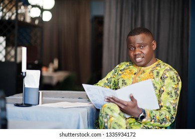 Friendly afro man in traditional yellow clothes at restaurant holding menu at hands and chooses the dishes.