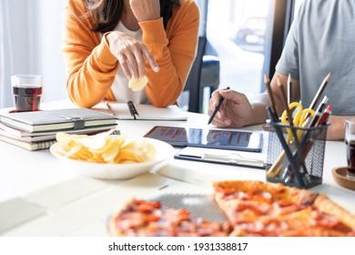 Freundliche asiatische Geschäftsteam-Kollegen, die zusammen Pizza und Kartoffelchips essen, haben Spaß beim Gespräch mit der Firmenfeier.