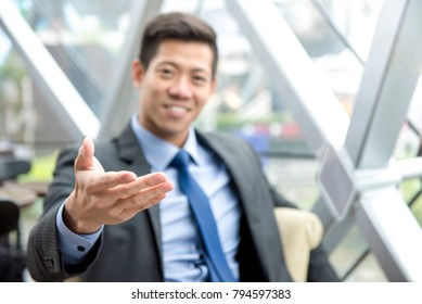 Friendly Asian businessman sitting in office lounge reaching out hand with open palm, welcome gesture