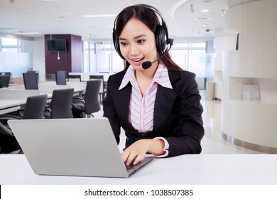 Friendly asian customer service with headset in a modern office