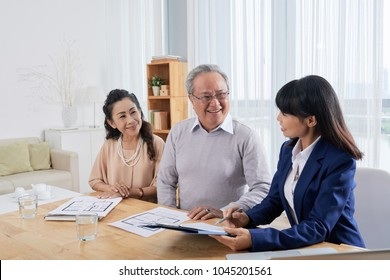 Friendly Asian estate agent sitting at spacious office with senior clients and helping them to fill in form in order to rent apartment