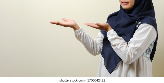Friendly Asian muslim girl showing something at her side with both hands, isolated on white background