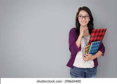 Friendly Asian teacher holding some books and looking to copy space on grey background