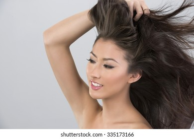 Friendly Asian young woman with long medium brown hair with hands on head