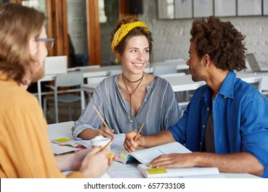 Friendly atmosphere and good relationships. Multiracial students doing their home assignment sitting in classroom. Young pretty student female trying to help her groupmate to catch with studying