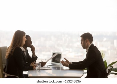 Friendly attentive hr managers interviewing vacancy applicant, multi-ethnic partners discussing new project idea sitting at office desk with cityscape outside, big window at background, side view