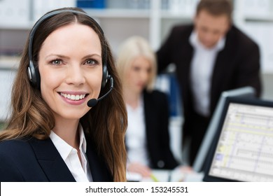 Friendly attractive young call centre operator or member of the client services team wearing a headset turning to give the camera a lovely warm smile