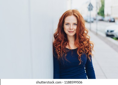 Friendly attractive young redhead woman relaxing leaning against a white exterior wall with copy space in an urban street staring at camera