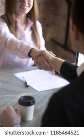 Friendly attractive young woman handshaking man at meeting. Deal with good result, start of work with business partner or customer, good relationship, recruitment, hiring process, HR concept. Close up