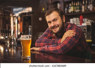 Friendly bearded bartender smiling joyfully to the camera, enjoying working at his beer pub, copy space. Happy brewer servind delicious beer, leaning on a counter. Service, lifestyle concept