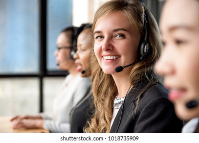 Friendly beautiful caucasian woman telemarketing customer service agent working in call center with her multiethnic team