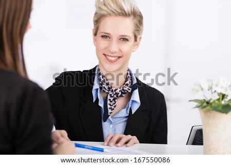 Friendly beautiful receptionist standing behind the counter assisting a guest to check into a hotel