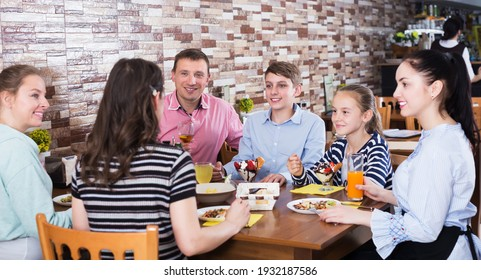 Friendly big family with kids meeting in cafe and enjoying dinner together