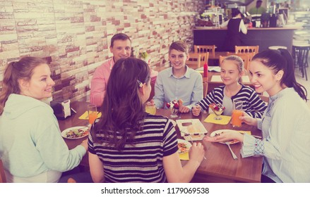 Friendly big family meeting in cafe and enjoying meal together. Focus on brunette