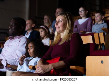 Friendly biracial family spending time together in cinema. Selective focus of young european woman sitting with cute preteen girl and aframerican man, absorbedly watching movie