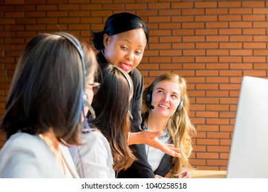 Friendly black businesswoman supervisor training work to her multiethnic colleagues in call center office