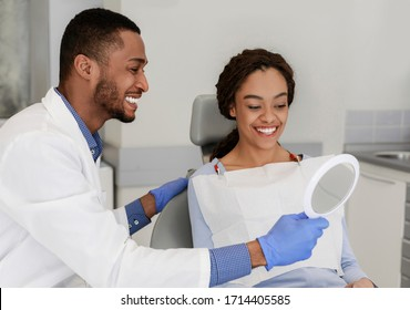 Friendly black dentist giving mirror to his happy female patient
