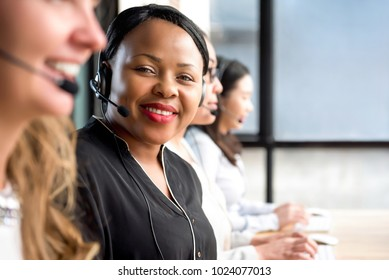 Friendly black woman wearing microphone headset working in call center with international team as telemarketing customer service agents