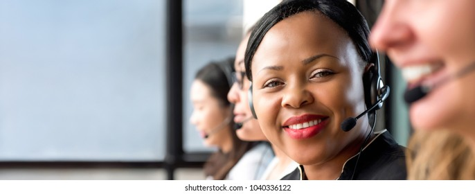 Friendly black woman wearing microphone headset working in call center with international team as telemarketing customer service agents, panoramic banner