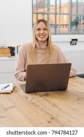 Friendly blond businesswoman with a big smile working on a laptop in a minimalist airy bright office