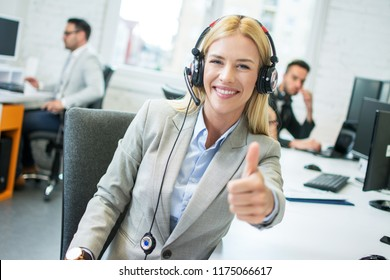 Friendly blonde female telephone worker with headset showing thumb up in office