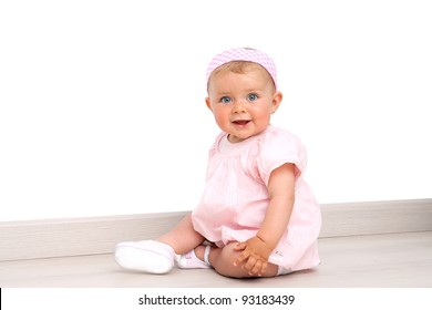 Friendly blue eyed baby girl wearing pink dress and pink head band sitting on the floor indoors