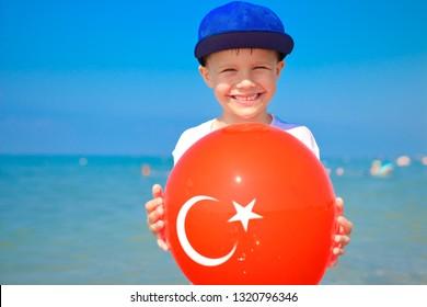 Friendly boy holding balloon with turkish flag on it. Tropical vacation in Turkey. Boy on sea beach