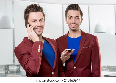 Friendly business brothers twins in red jackets using mobile phone in white office