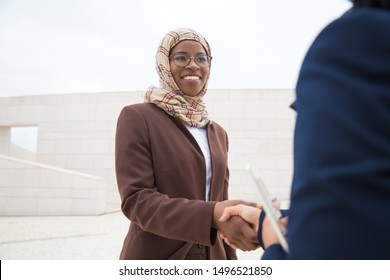 Friendly business lady meeting and thanking coworker outside. Muslim business women in hijabs standing outdoors and shaking hands with each other. Muslim women in business concept