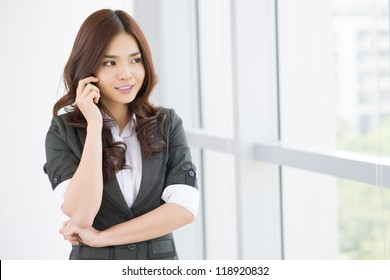 Friendly business lady talking to the client by mobile phone