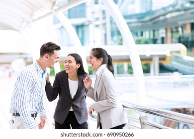 Friendly business meeting concept. Outdoor business meeting with two beautiful women and white male talking together discussing business plan. Taken outdoor in natural lights.
