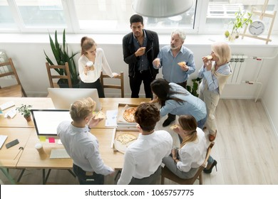 Friendly business team of diverse young and senior people enjoy eating pizza together, employees group talking sharing meal in office, food delivery service at lunch time concept, top view overhead