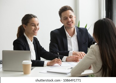 Friendly business team members chatting laughing together during office break, happy coworkers talking having good relations and pleasant conversation at work, smiling hr interviewing job applicant