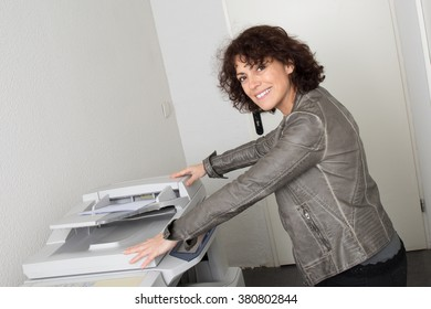 Friendly business woman smiling at the office with printer