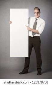 Friendly businessman holding and pointing finger at white empty vertical panel with space for text isolated on grey background.