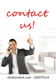Friendly businessman pointing Contact Us in the office