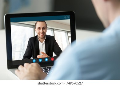 Friendly businessman smiling from laptop screen, video call with human resources. HR interviews casually dressed job applicant, Boss communicates with remote employee. Close up, view over shoulder.
