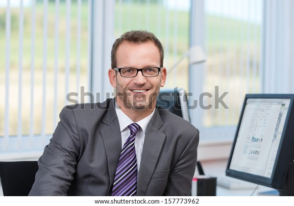 Friendly businessman wearing glasses sitting at his desk in the office looking at the camera with a smile