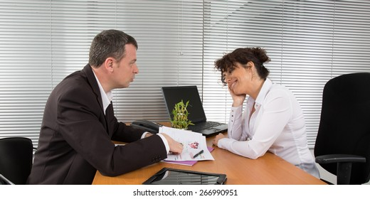 Friendly businessman and woman sitting at a desk