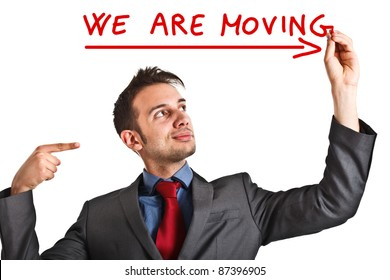 """Friendly businessman writing """"We are moving""""on the screen"""