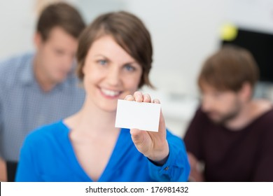Friendly businesswoman holding up a blank card for your credentials or contact details with focus to the card