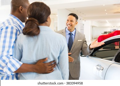 friendly car dealer showing new car to customers