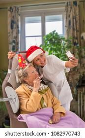 friendly care giver wearing Santa ' hat embracing senior woman
