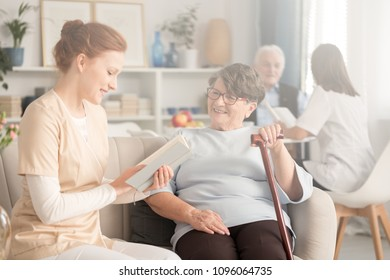 Friendly caregiver reading a book to a happy elderly woman with a walking stick at a sanatorium
