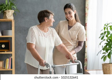 Friendly caregiver supporting a senior patient using walking frame