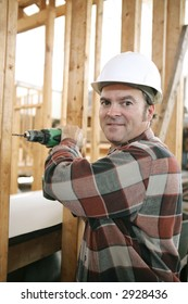 A friendly carpenter drilling on a construction site.  Vertical view with room for text.