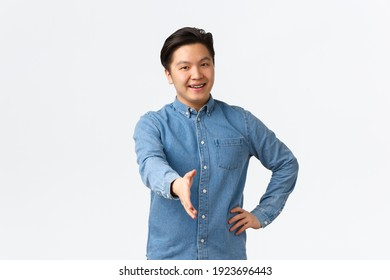 Friendly cheerful asian man searching for job, come to interview, extending hand for handshake, greeting someone, welcome to office, saying hello with happy smile, white background