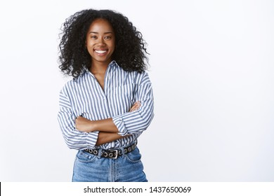 Friendly cheerful attractive african american curly-haired young 25s woman consultant woking talking coworkers smiling pleasant having fun enjoying relaxing company mood, standing hands crossed chest