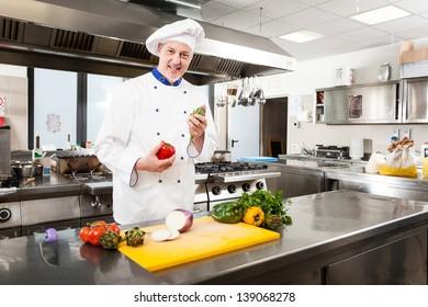 Friendly chef preparing vegetables in his kitchen