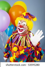 Friendly circus clown holding a bunch of balloons and waving hello.